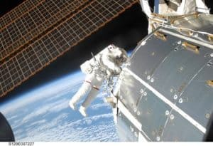 An astronaut conducting a spacewalk outside the International Space Station